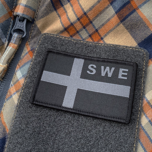 A Sweden Flag OPS Nylon Black/Grey Patch seen slightly from the side mounted with velcro on a shirt