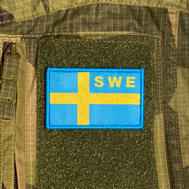Sweden Flag OPS Blue Yellow Patch mounted on a M90 camouflage shirt sleeve
