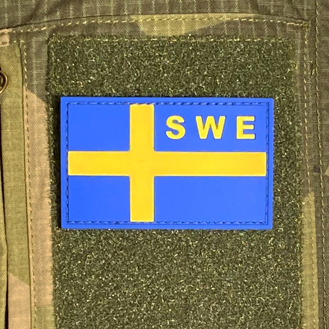 Sweden Flag OPS PVC Blue Yellow Patch mounted on a M90 camouflage shirt sleeve