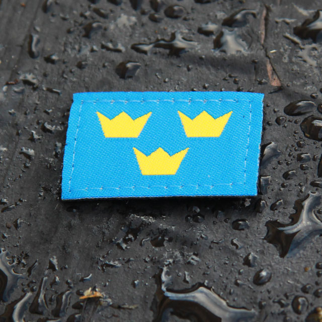 Three Crowns Morale Patch on wet background.