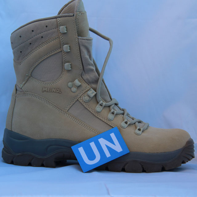 Showing the size of a United Nations Hook Patch Large with a desert boot as background.