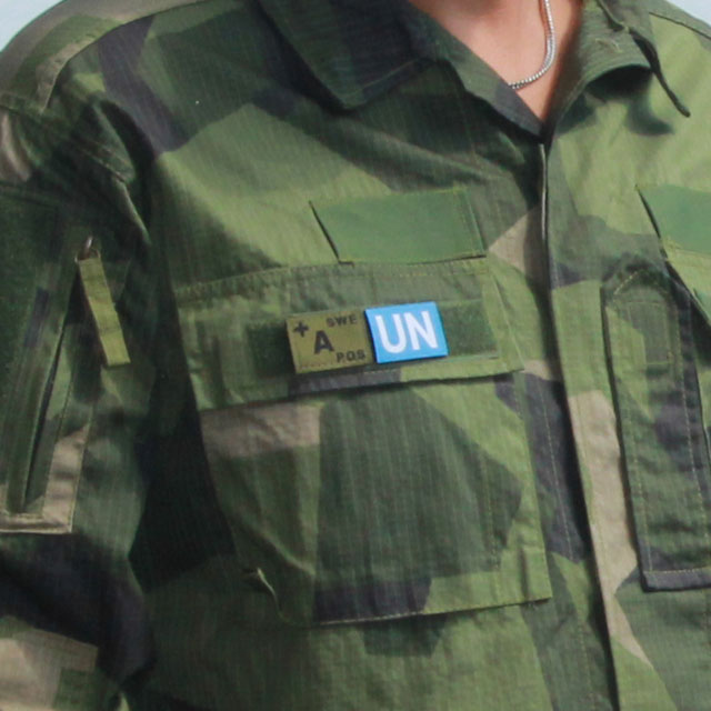 A United Nations Hook Patch Small mounted on the breast pocket of a Field Shirt M90.