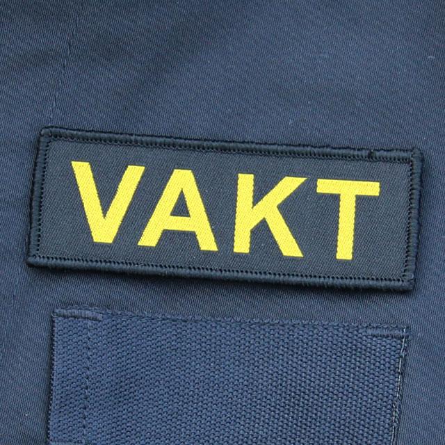 Ett VAKT Kardborremärke mot en bakgrund av Marinens uniformsjacka.