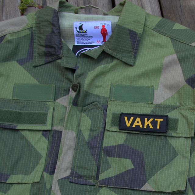 Ett VAKT Kardborremärke monterat på locket på en bröstficka på en M90 kamouflage jacka.