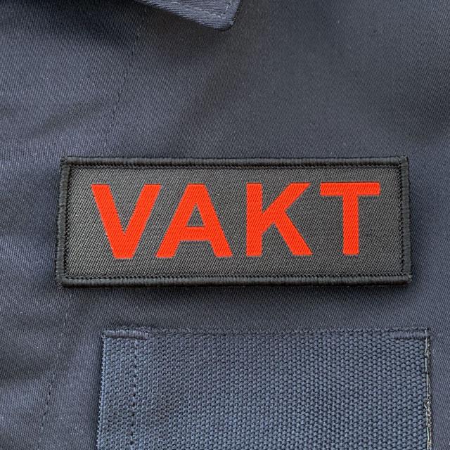 VAKT Röd text Kardborremärke mot blå jacka