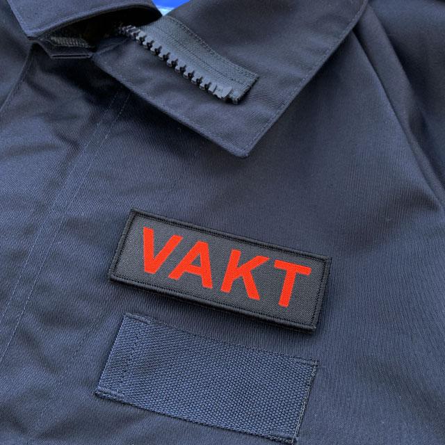 VAKT Röd text Kardborremärke produktfoto