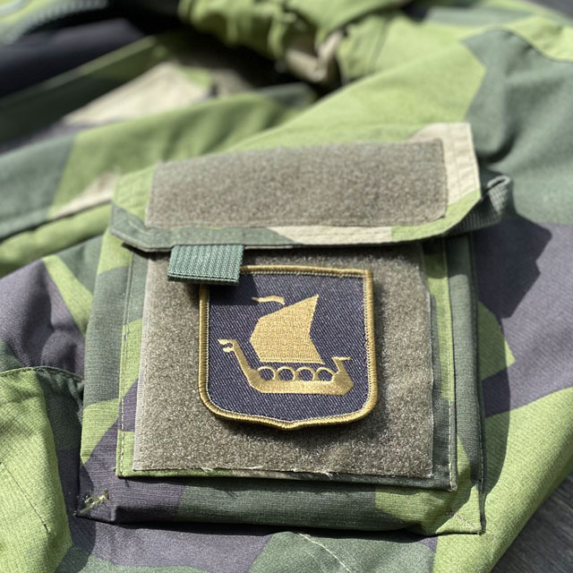 A Viking Ship Shield Large Olive and Black Hook Patch seen from an angle mounted on a NCWR Jacket M90