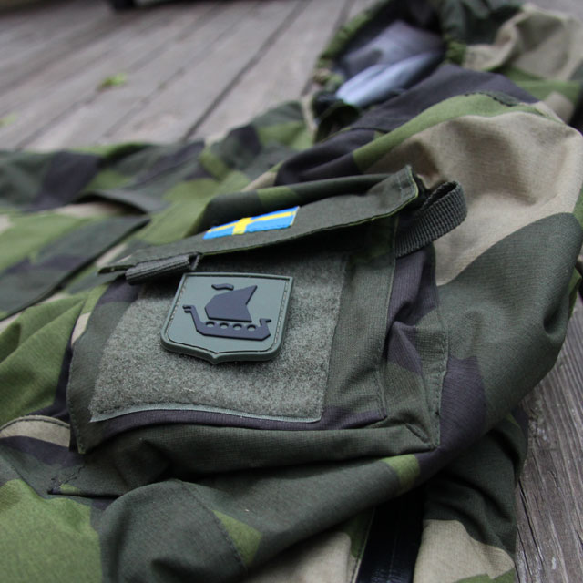M90 kamouflage jacka och ett Vikingship Shield Hook PVC Green/Black Patch märke.