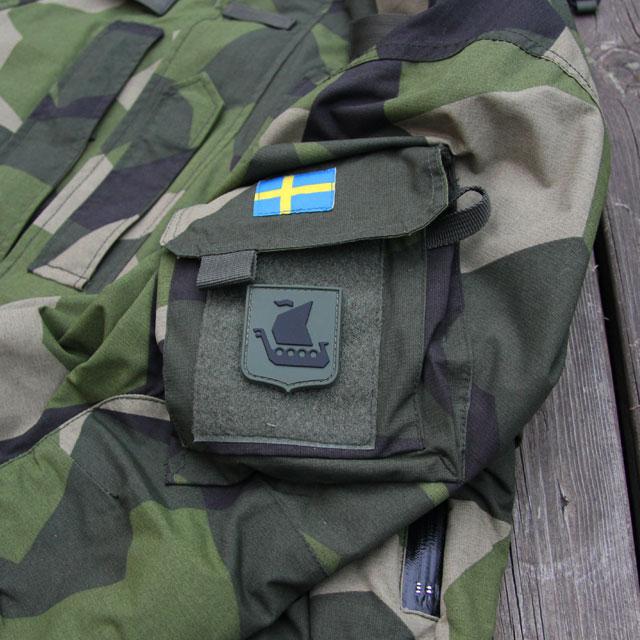 En Svensk flagga och ett Vikingship Shield Hook PVC Green/Black Patch märke på en NCWR Jacket M90.