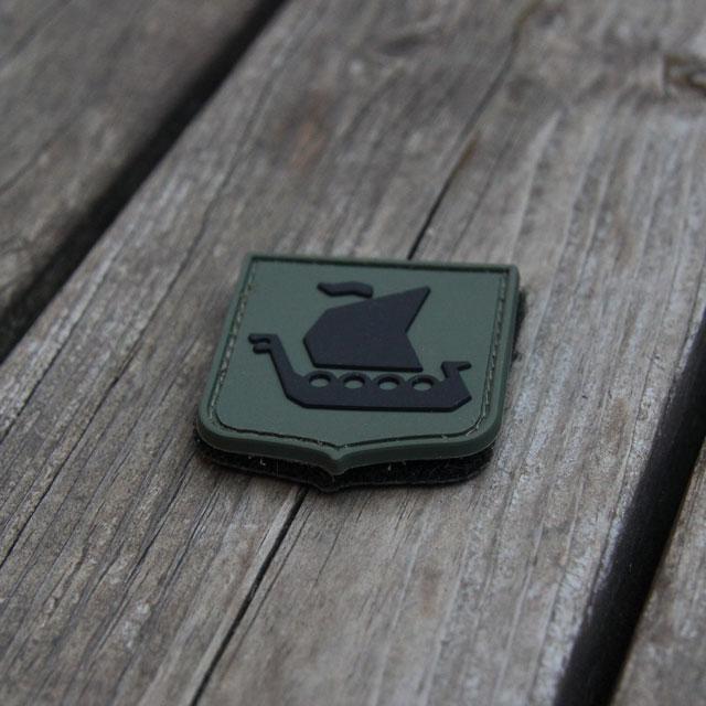 Sedd snett uppifrån är vårt Vikingship Shield Hook PVC Green/Black Patch märke mot en bakgrund av trä.