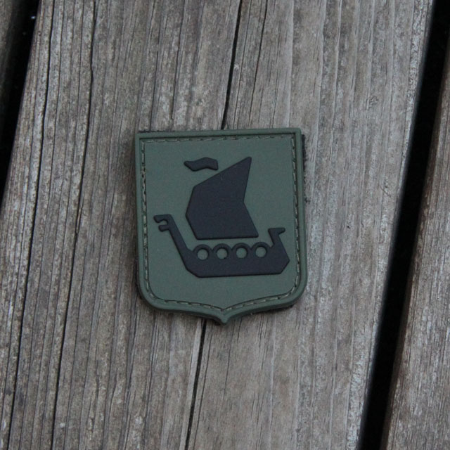 Ett Vikingship Shield Hook PVC Green/Black Patch mot en träbakgrund.
