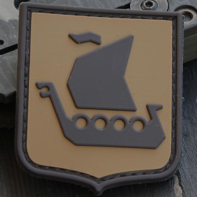 Bilden visar en närbild på ett Vikingship Shield Hook PVC Desert Patch märke.