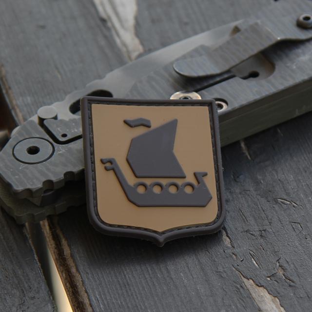 En Strider kniv används som stöd och storleksjämförelse vid produktfotografering av ett Vikingship Shield Hook PVC Desert Patch märke.