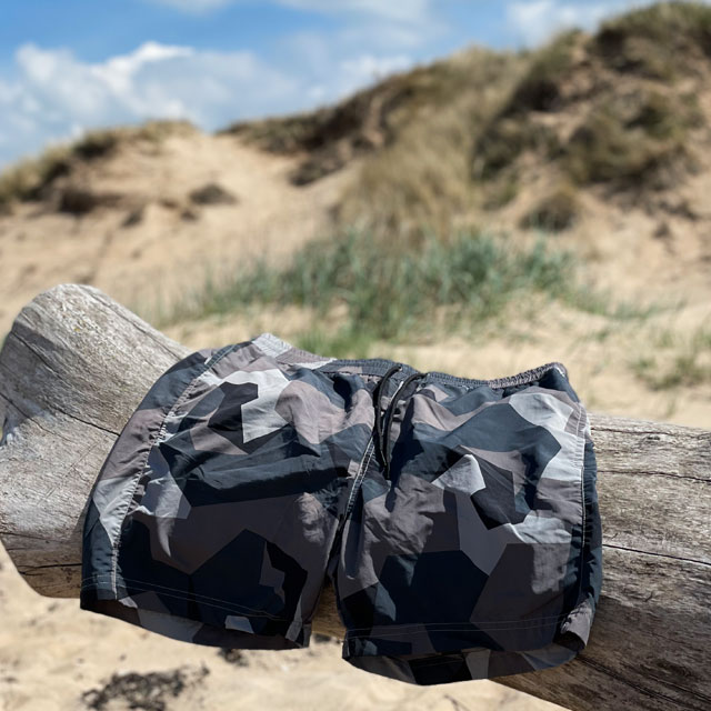 A pair of POSEIDON Swim Shorts M90 Grey from TAC-UP GEAR hanging on a log on a beach