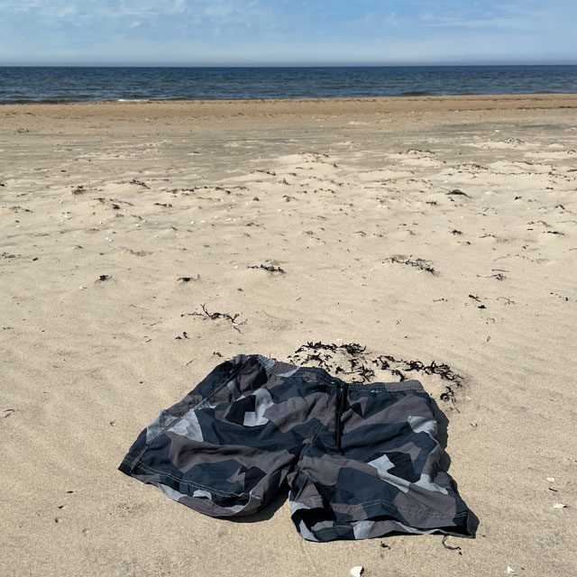 A pair of POSEIDON Swim Shorts M90 Grey from TAC-UP GEAR lying in the sand on a beach