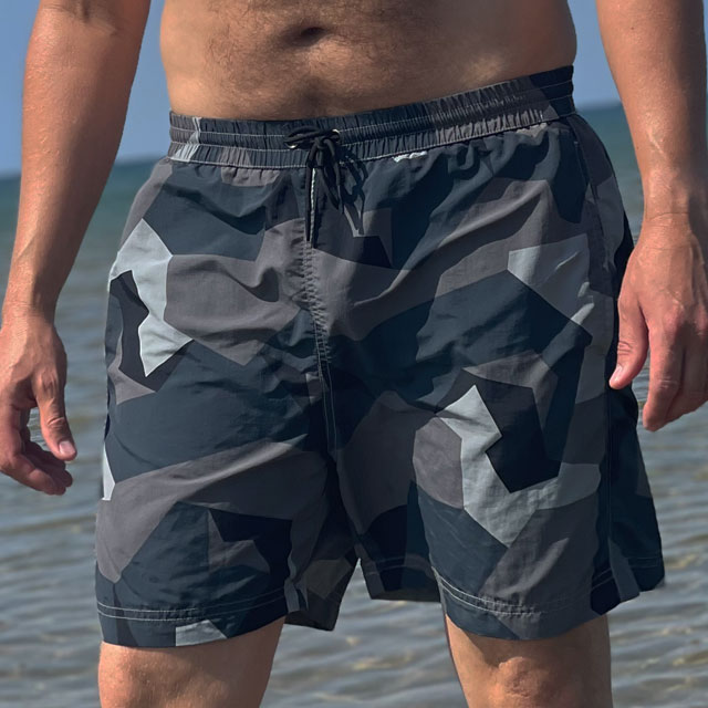 POSEIDON Swim Shorts M90 Grey seen from the front on model with ocean as background