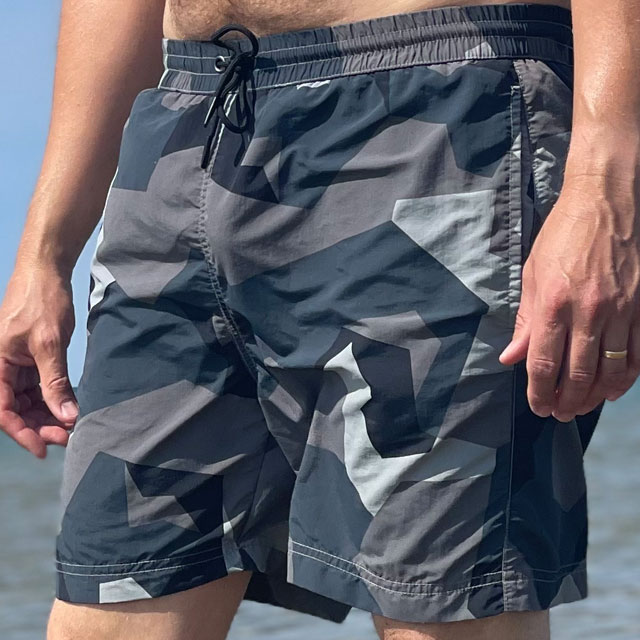 POSEIDON Swim Shorts M90 Grey seen from the front at a slight angle on model with ocean as background