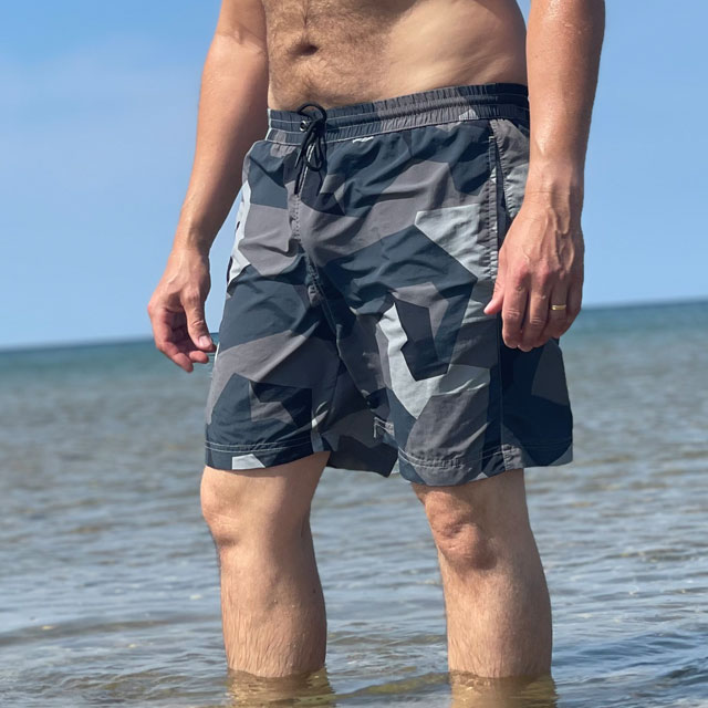POSEIDON Swim Shorts M90 Grey seen from the front on model in the sun with ocean as background