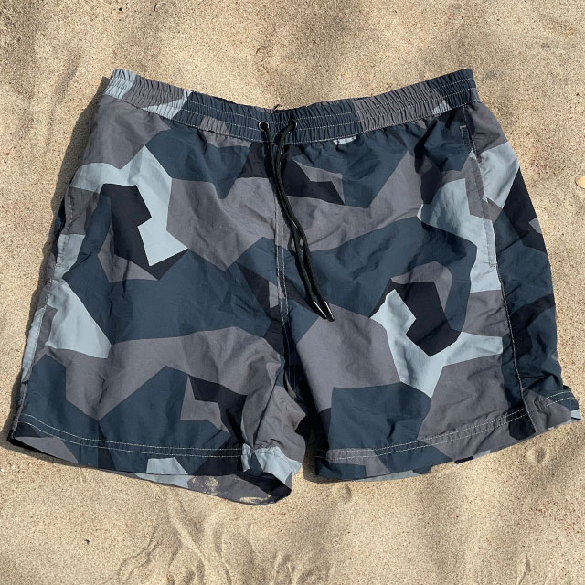 POSEIDON Swim Shorts M90 Grey lying flat on the beach seen from above