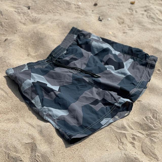 POSEIDON Swim Shorts M90 Grey lying flat on the beach seen at an angle