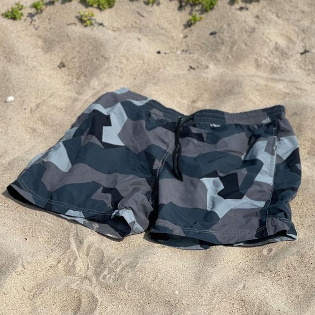 A closer look at a pair of POSEIDON Swim Shorts M90 Grey lying flat on the beach