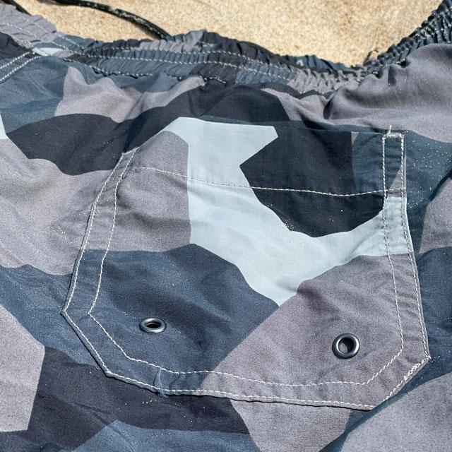 The backpocket on a pair of POSEIDON Swim Shorts M90 Grey lying flat on the beach