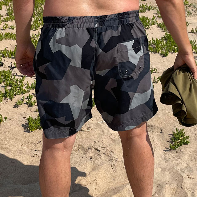 POSEIDON Swim Shorts M90 Grey from TAC-UP GEAR on model seen from the back on the beach in the sun