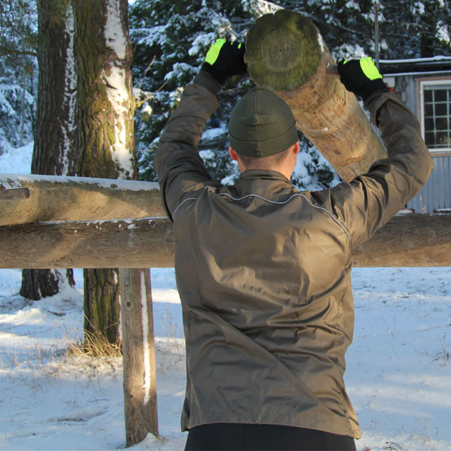Lifting outdoors at the training area wearing a Running Jacket Green.