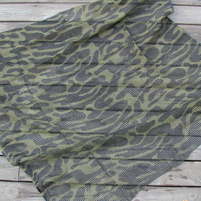 A Scrim Scarf Black/OD Camo laying against a wooden bakground showing its pattern.