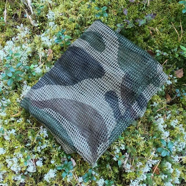 A folded Scrim Net Scarf FR Commando on the Swedish forest floor