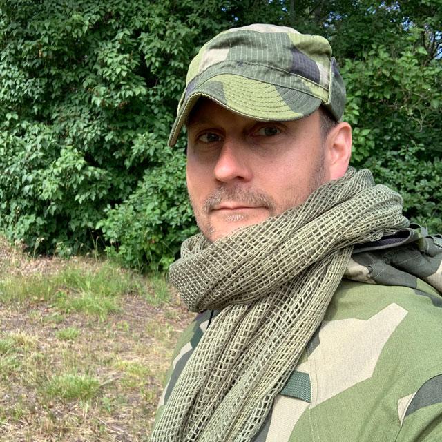 A Scrim Net Scarf Green worn around the neck