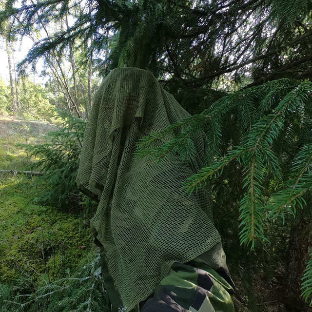Showing the excellence in camouflage wearing a draped Scrim Net Scarf Green draped and in the Swedish forest