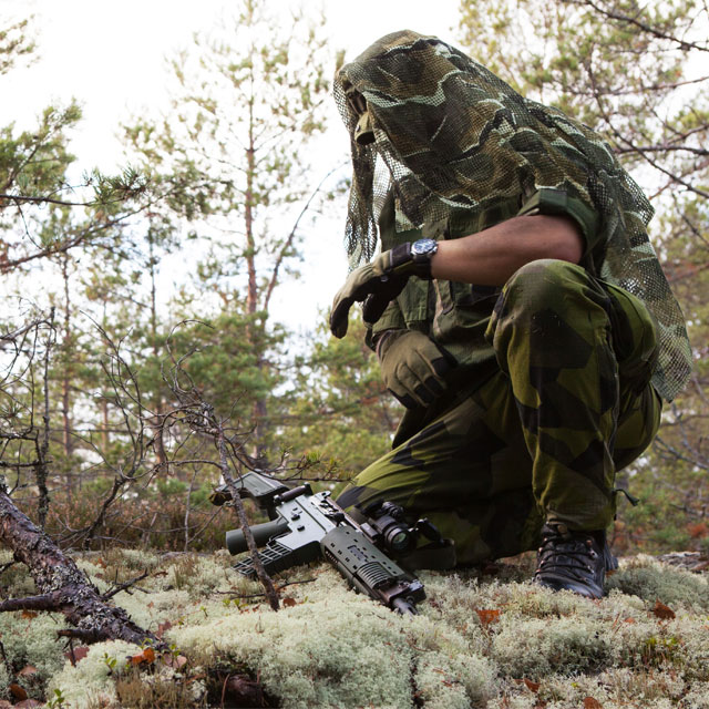 The Scrim Scarf M90 is draped over a Boonie Hat M90 and used as camouflage.