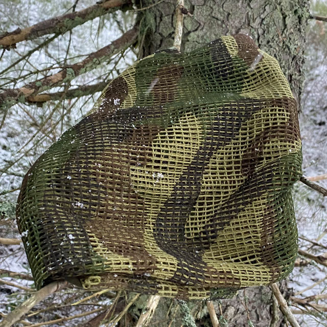 a Scrim Net Scarf Woodland on branches of a tree