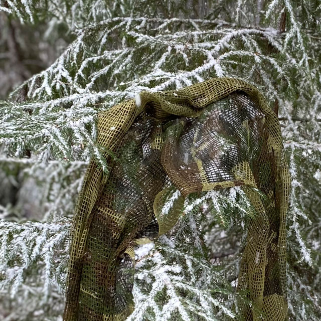 a Scrim Net Scarf Woodland on branches of a tree with snow on