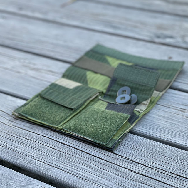Sewing Case M90 from TAC-UP GEAR seen open from an angle lying flat on wooded floor