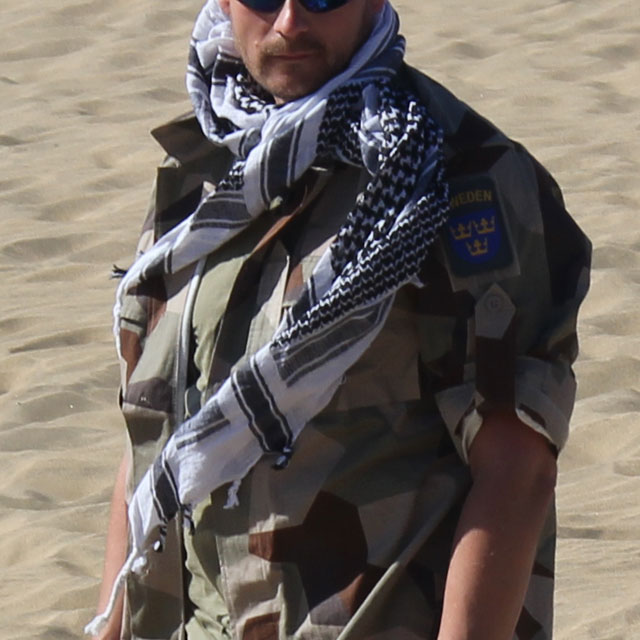 A Shemagh Black/White is worn together with a M90K Desert camouflage jacket in the sunny desert.