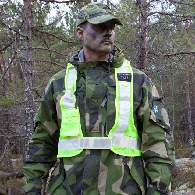 En Skyddsvakt Reflexsväst buren över en M90 kamouflage jacka och visar framsidan.