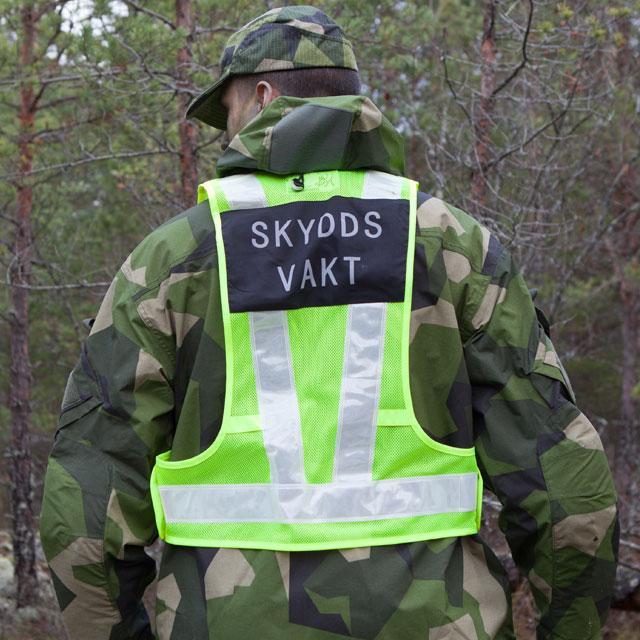En bild som visar ryggen av en buren Skyddsvakt Reflexsväst över M90 kamouflage jacka.