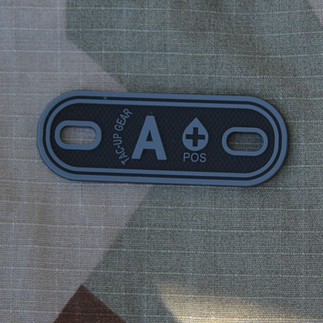 A+ Bloodtype Tag Black PVC with M90 camouflage background.