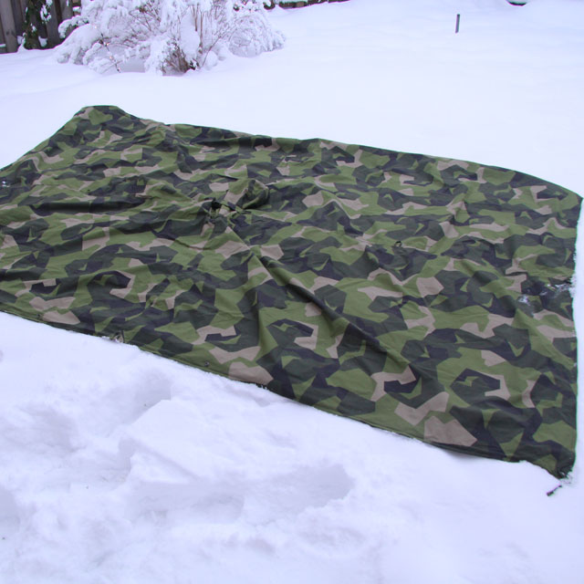 Rectangle Tarp Poncho M90 spread out outdoors on wintery ground.