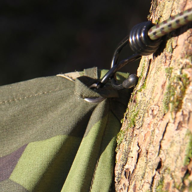 Use elastic rope and hooks to easily fasten the Tarp Poncho M90 in its eyelets.