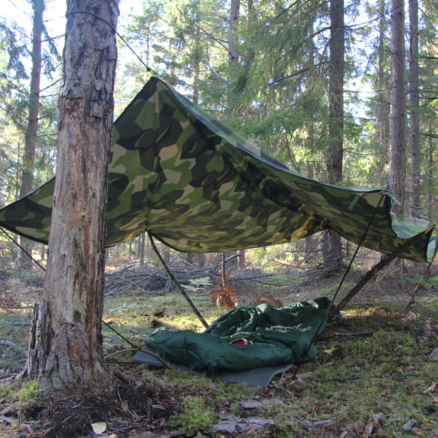Tarp Poncho M90 used as roof ofver a sleepingmat and sleepingbag in the Swedish forest.