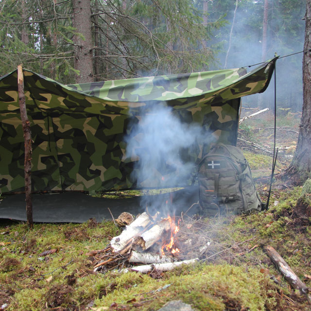L-shape configuration of the Tarp Poncho M90 with a camp fire burning in the Swedish forest.