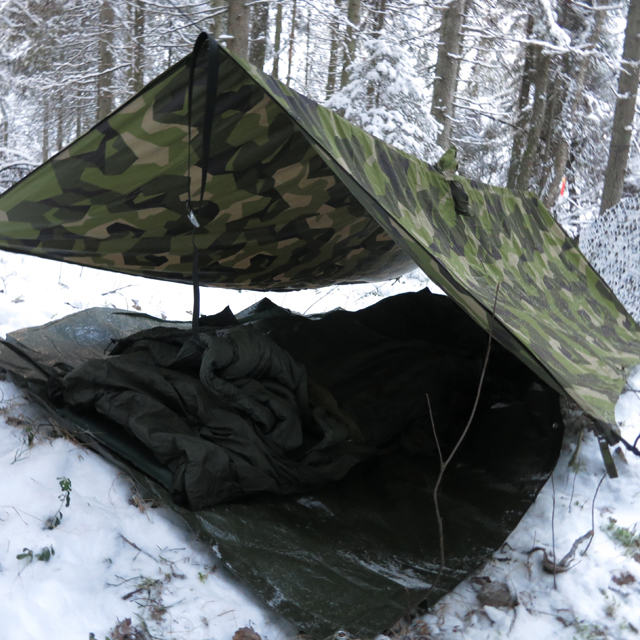 Winter usage of the Tarp Poncho M90 seen here as roof over sleepingbag and sleepingmat on the snow covered ground.