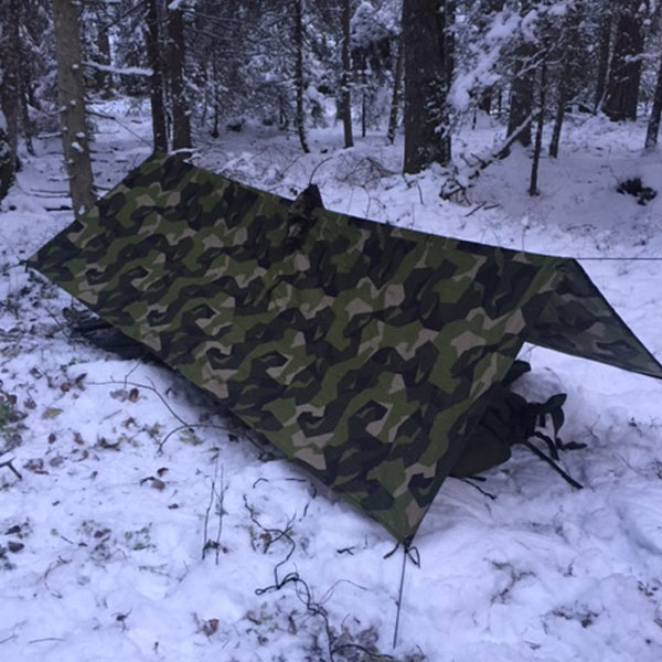 Shelter set up using a Tarp Poncho M90 in Swedish winter scenery.