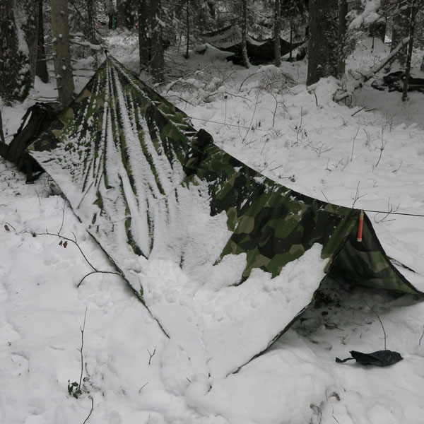 Snowdrift caked on the side of a Tarp Poncho M90 used as basha for the nigh in Swedish winter.