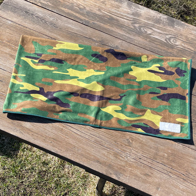 A Towel Camouflage from TAC-UP GEAR folded on a wooded table