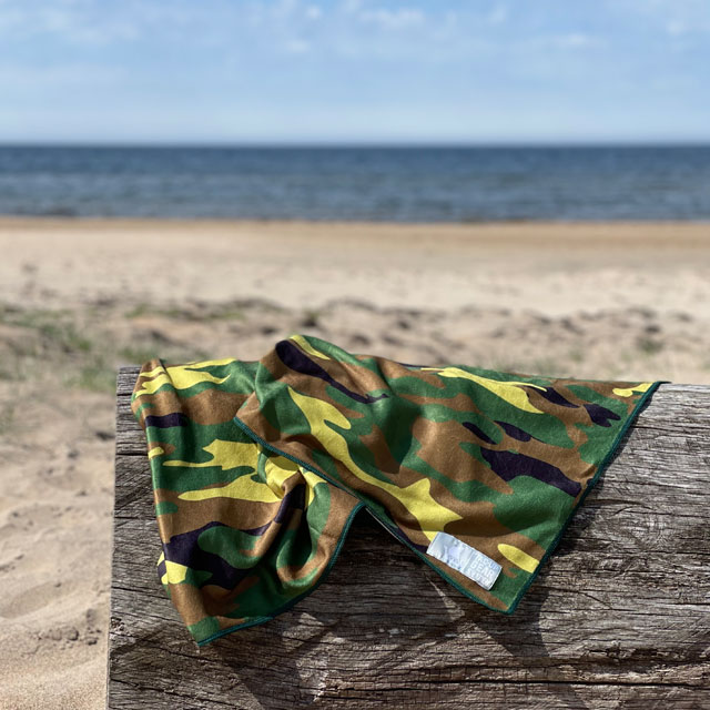 A Towel Camouflage from TAC-UP GEAR on a log at the beach