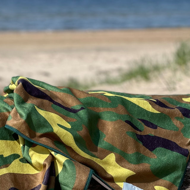 A closer look at a Towel Camouflage from TAC-UP GEAR lying on a log at the beach